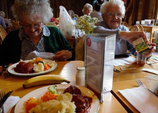 Iäkkäitä ihmisiä ruokailemassa yhdessä.