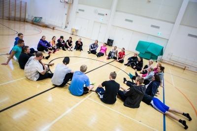 Valokuvassa ihmiset istuvat piirissä liikuntasalin lattialla (loppupiiri).