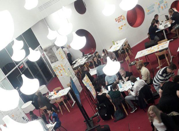 Ihmisiä istumassa ryhmissä pöytien ympärillä. Valokuva.