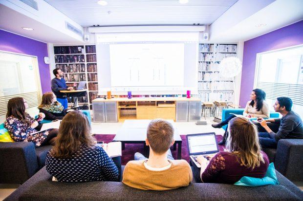 Opettaja luennoi pienryhmälle kirjastomaisessa tilassa.