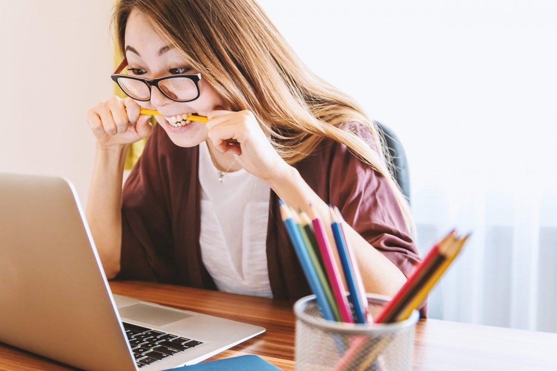 Nuori henkilö katsoo kannettavan tietokoneen ruutua ja pureskelee kynää. Etualalla on värikyniä purkissa.