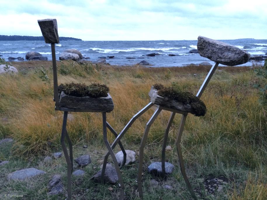 Kaksi tuolia meren äärellä vastakkain.