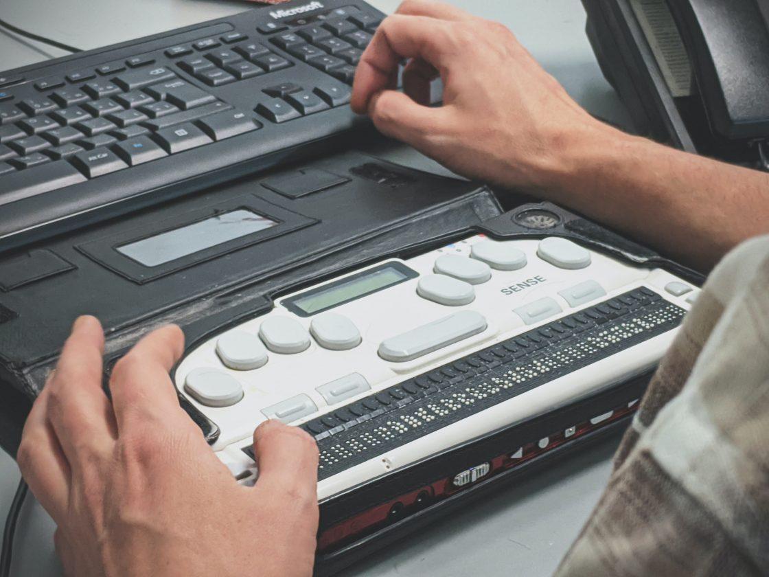Henkilö käyttää Braille-pistekirjoitusnäyttöä.