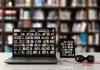 Läppäri, tabletti ja kännykkä, joista näkyy kirjahylly täynnä kirjoja. Taustalla samassa tilassa oleva kirjahylly.