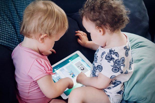 Kaksi lasta pelaa yhdessä mobiilipeliä tabletilla.