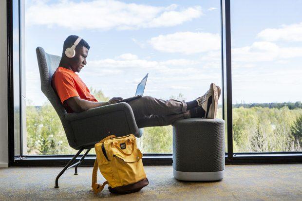Opiskelija istuu taaksepäin nojaten, jalat rahilla, läppäri sylissä ja kuulokkeet korvilla. Vieressä lojuu keltainen reppu.
