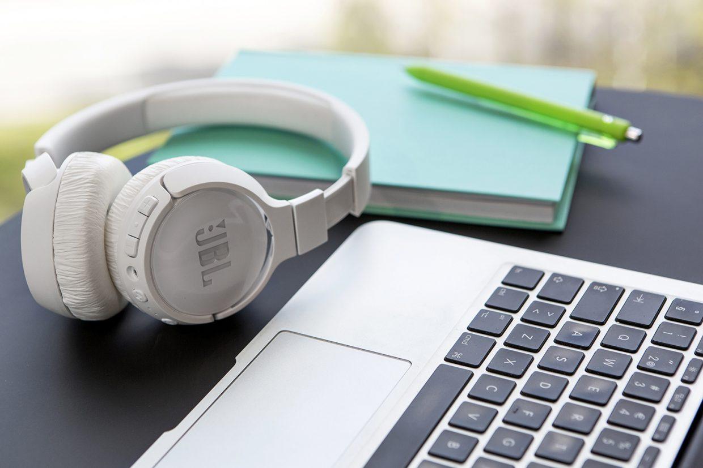 Pöydällä on Applen läppäri, langattomat kuulokkeet sekä turkoosi muistikirja ja kynä.