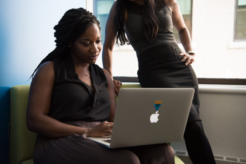 Tumma naisoletettu asiantuntija istuu kannettava tietokone sylissään ja näyttää ruutua hänen takanaan seisovall kollegalle.