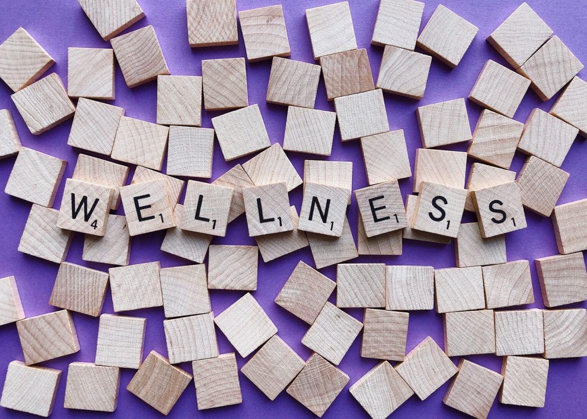 """Sana """"wellness"""" muodostettuna puupalikoista."""