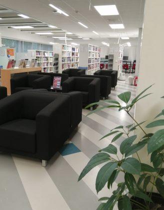 Nojatuoleja ja kirjahyllyjä sekä kasvi Karamalmin kampuksen kirjastossa.