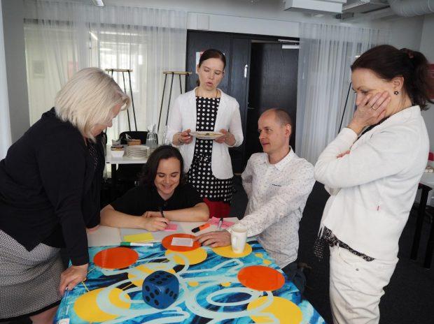 Viisi Osuma-hankkeen ohjausryhmäläistä pöydän ympärillä pelaamassa istuen ja seisten.