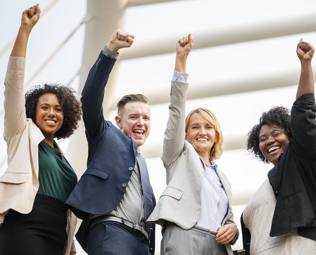 Neljä nuorta ihmistä seisoo rivissä puvut ja jakkupuvut päällä hymyillen nyrkit ilmaan nostettuna riemukas tunnelma.