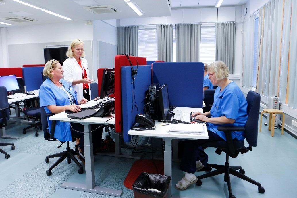 Hoitajapukuisia työntekijöitä toimistossa