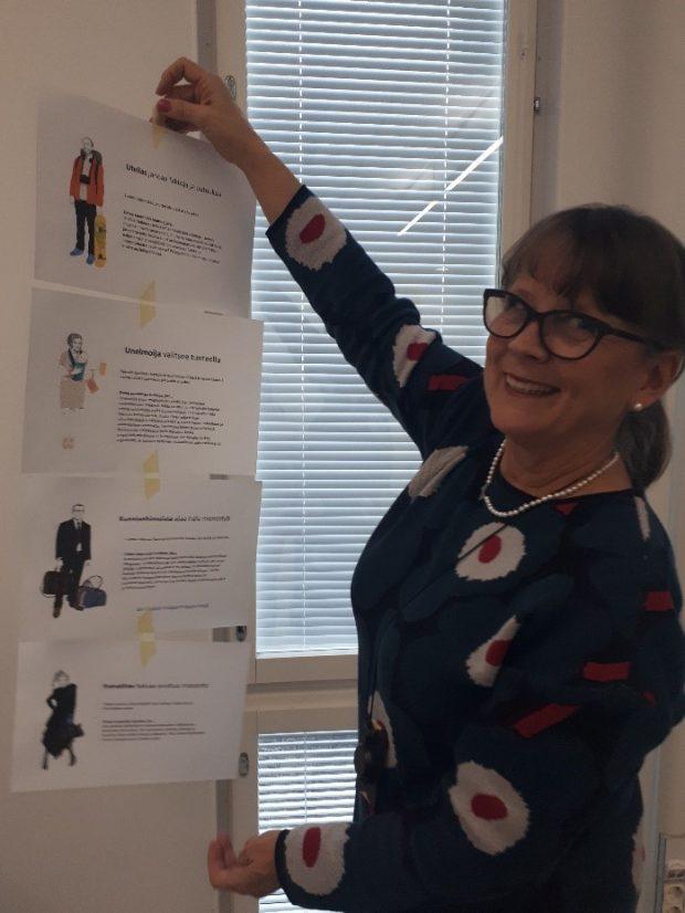 Sirkka-Liisa Kolehmainen poseeraa luokkahuoneessa taulun edessä.