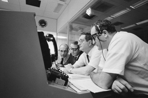 Apollo 13 lento, NASA, neljä miestä istuu rivissä ja tarkkailee monitoria,16 huhtikuuta 1970, etualalla lankapuhelin, mustavalkoinen.