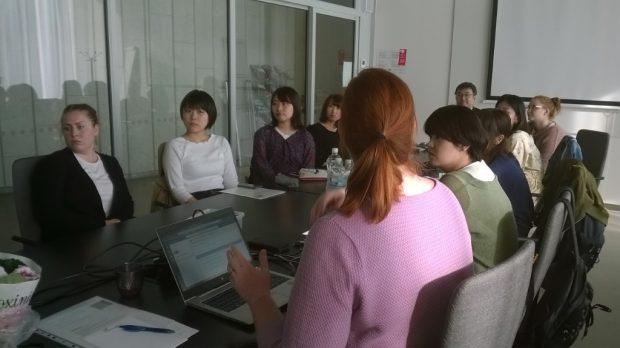 Kokoushuone, ihmisiä istumassa pöydän äärellä