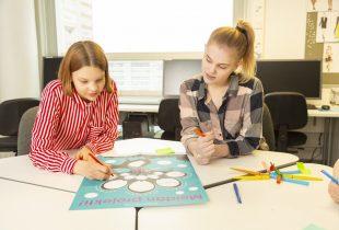 Luokkahuone, kaksi kouluikäistä lasta istuu rinnakkain, pöydällä juliste.