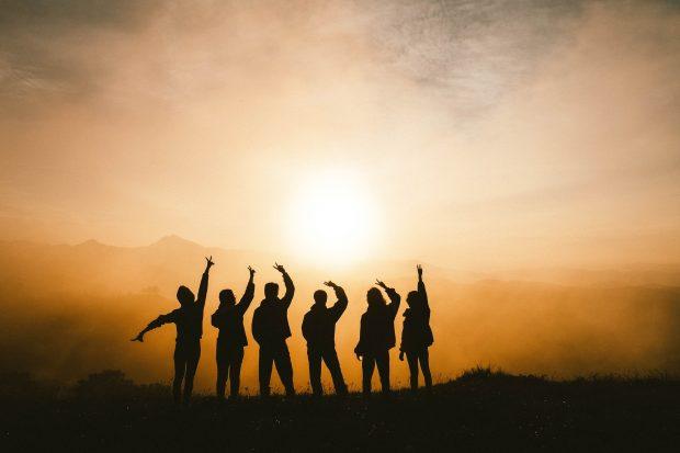 siluettikuva kuusi ihmistä seisoo rivissä taustalla aurinko