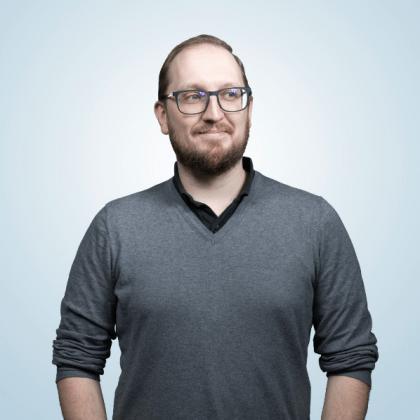 Silmälasipäinen parrakas mieshenkilö puolikuvassa vaaleaa taustaa vasten tummanharmaassa paidassa.
