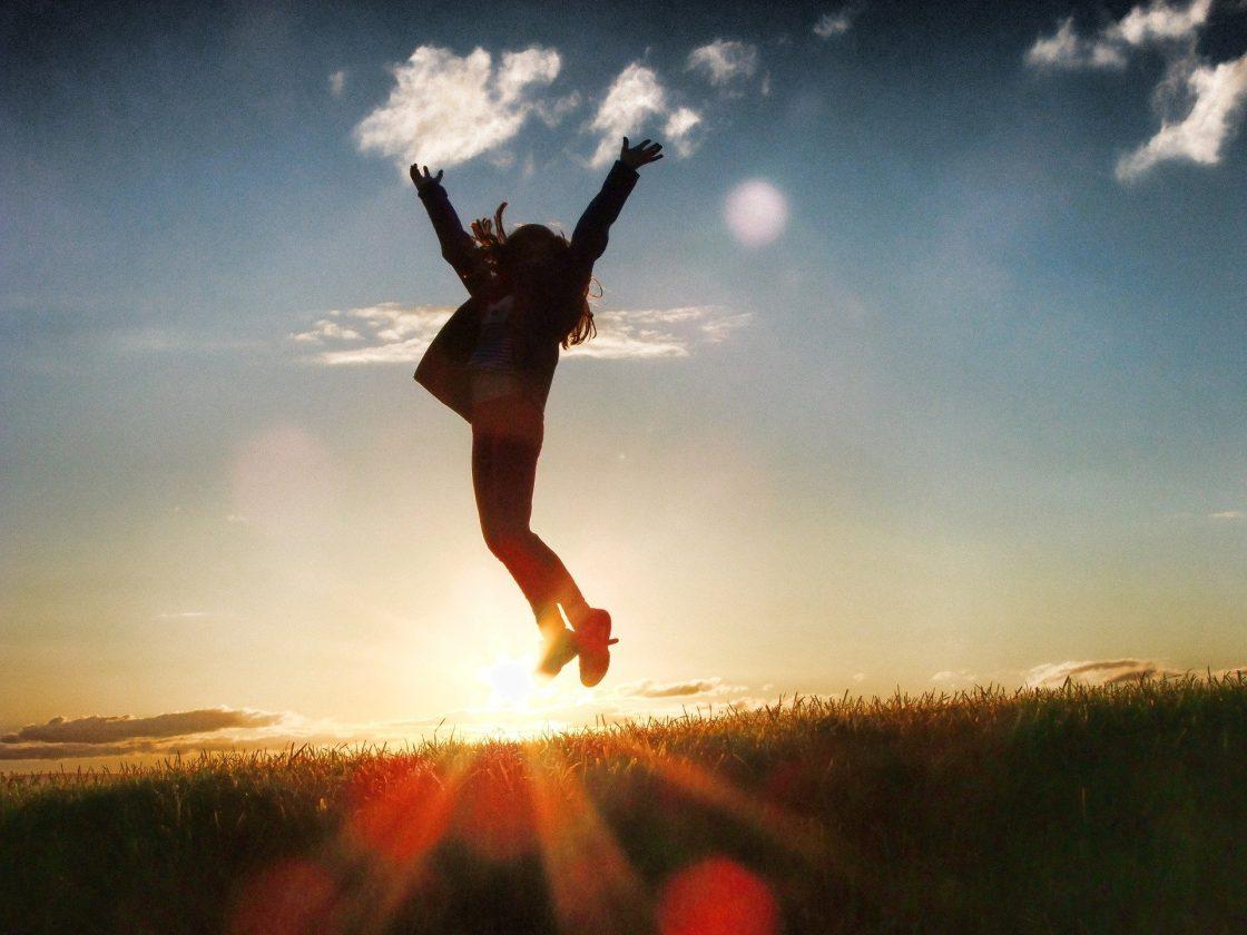 siluetti henkilöstä joka hyppää korkealle ilmaan, taustalla auringonnousu ja taivasta