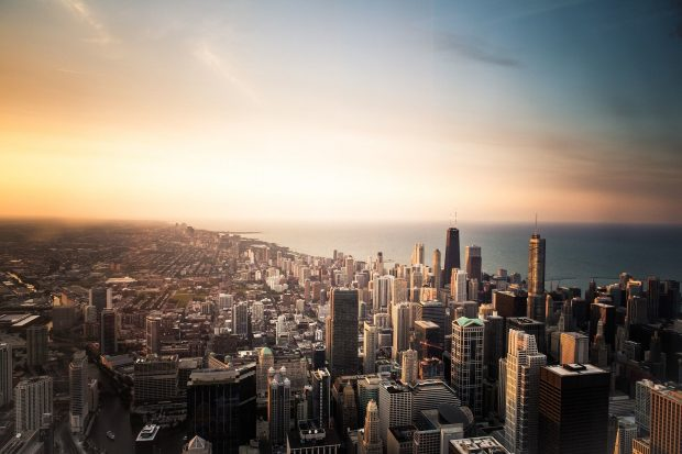 A city from the bird perspective, sky lit in light, sunrise in horizon