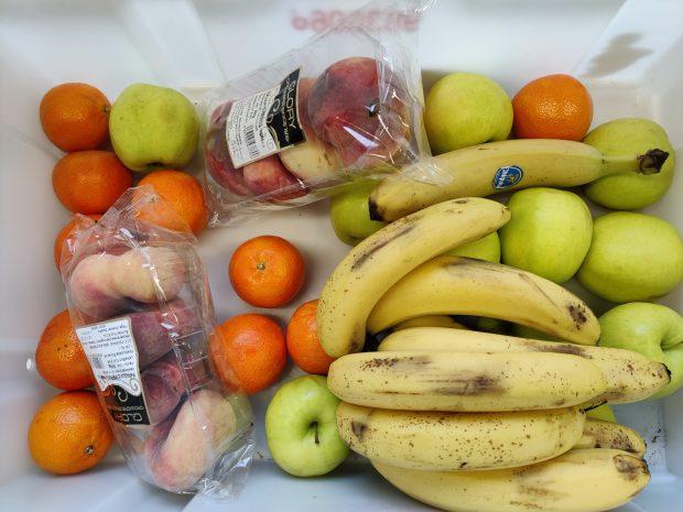hivenen ylikypsiä hedelmiä, banaaneja, omenoita ja sitrushedelmiä valkoisella alustalla