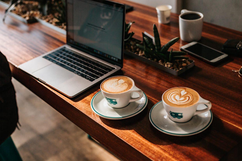 Kaksi kahvikuppia sekä kannettava tietokone