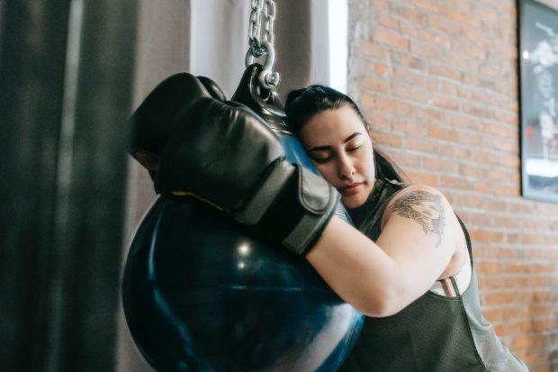 Väsynyt nyrkkeilijä halaa nyrkkeilysäkkiä